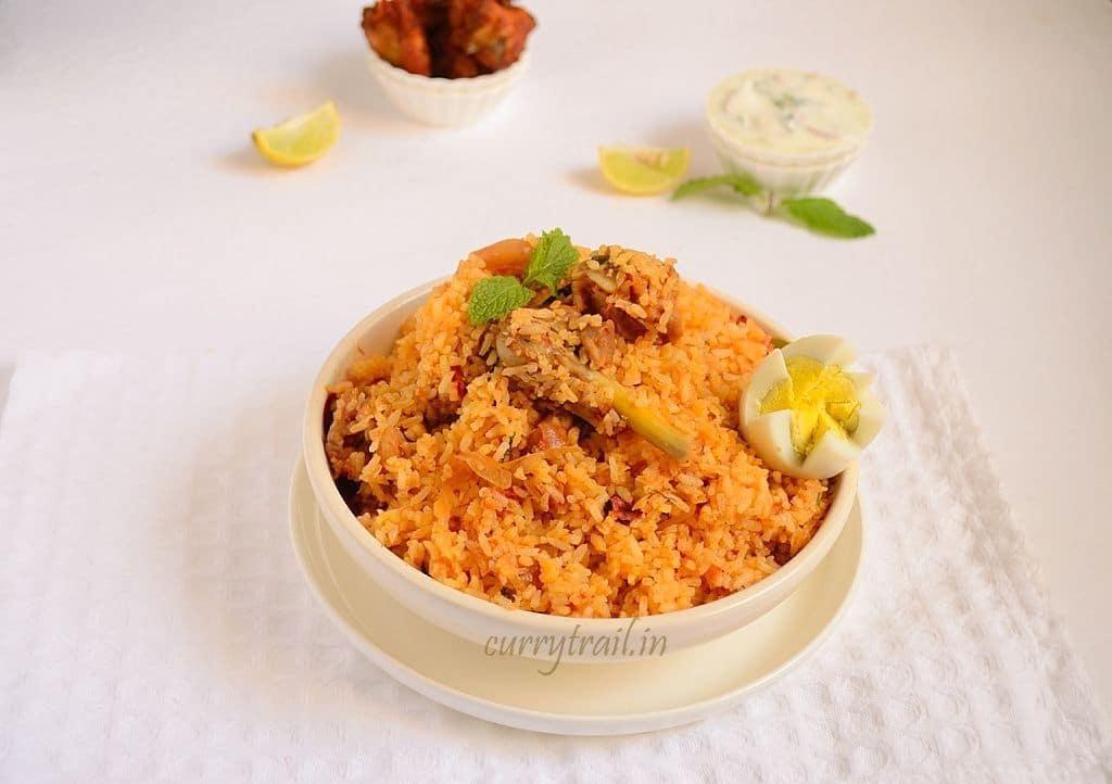Ambur chicken biryani in a white bowl and raita on the side