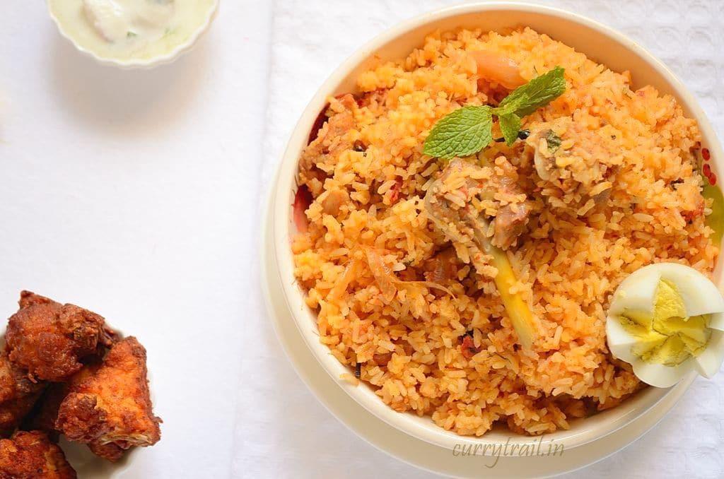 Ambur chicken biryani in a white bowl and fried chicken on the side