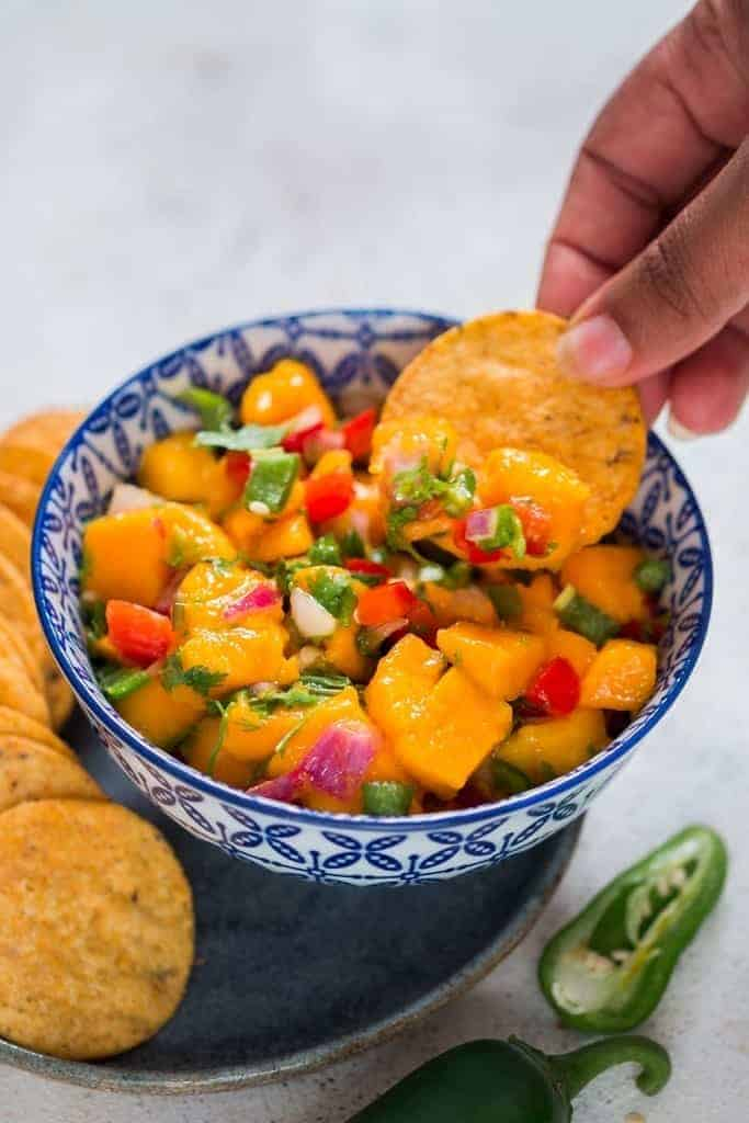 Finger scooping out mango salsa from a blue bowl with nachos chip