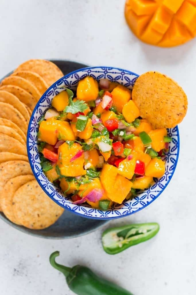 A bowl with fresh mango salsa with nacho chips on the plate near