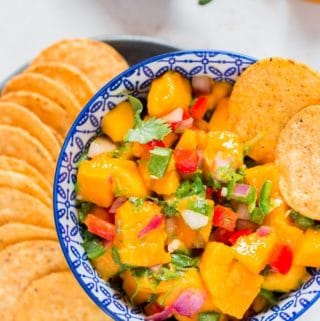 Easy to make mango salsa recipe in blue stripped bowl with nacho chips arranged on a plate near