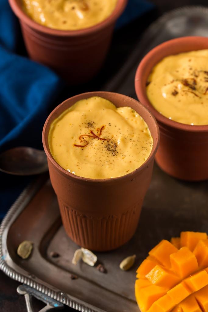 2 glasses of mango lassi recipe served in earthen glass