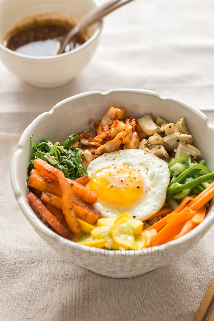 vegetarian Korean bibimbap with quinoa and vegetables in white bowl