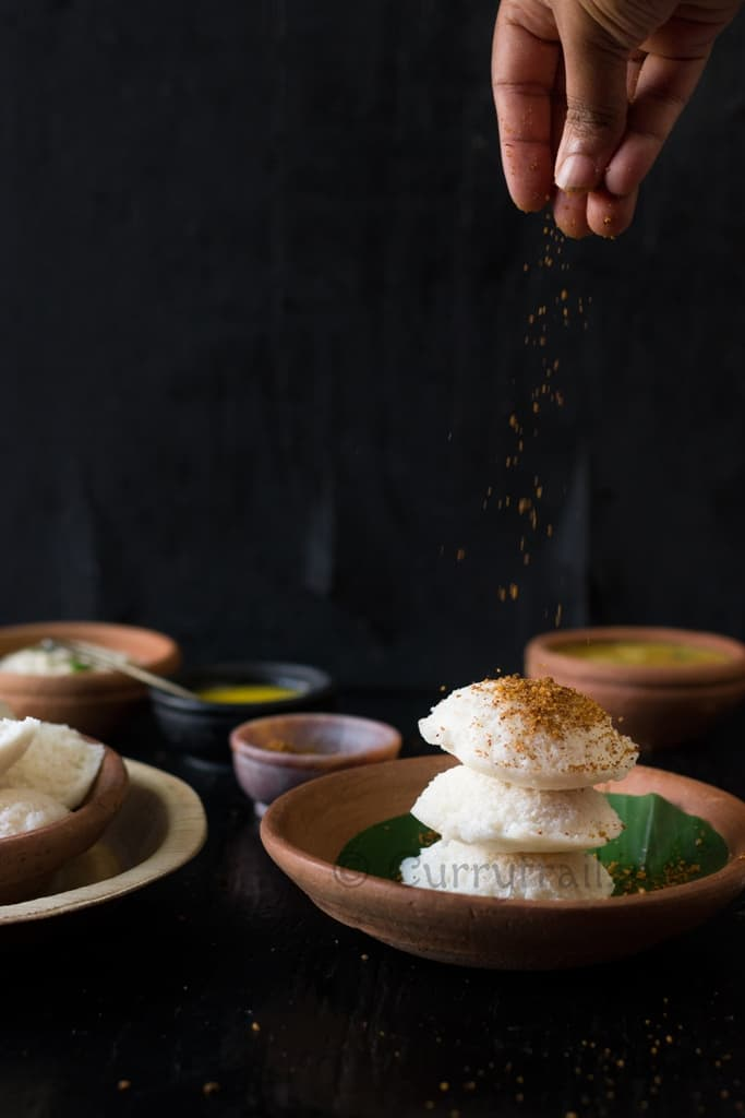 Idli stacked and idli podi sprinkled on top
