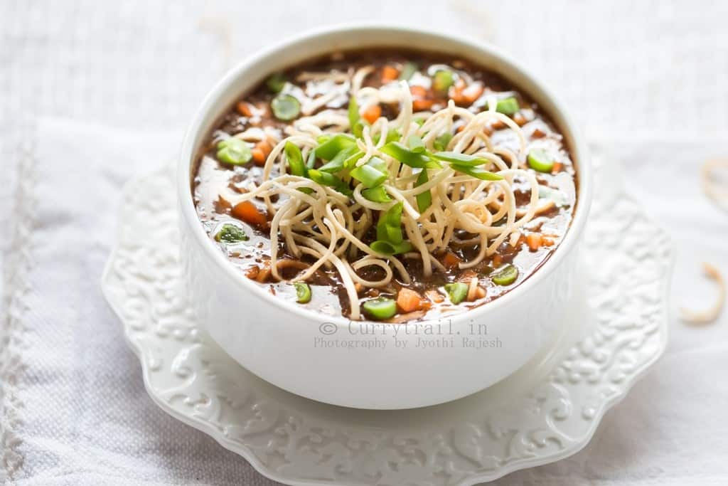 hot sour and spicy vegetable manchow soup topped with crunchy fried noodles served in white bowl