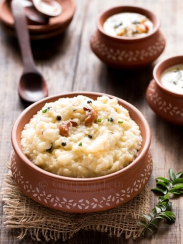 ven pongal is rice and moong dal breakfast dish served in earthen pots along side coconut chutney and sambar