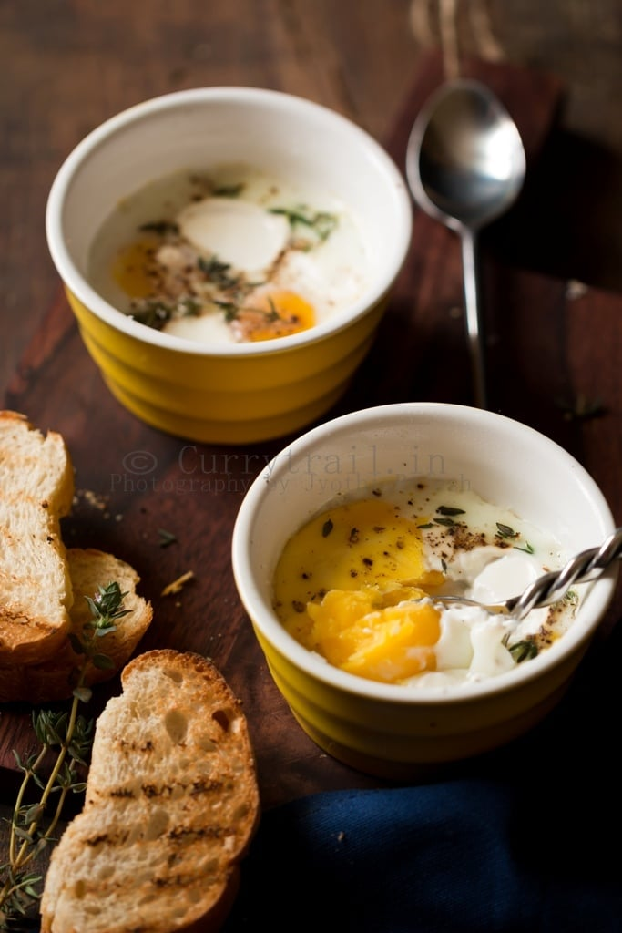 Baked eggs for breakfast with spoon scooping out the eggs