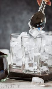 Filling glass with ice for iced coffee recipe