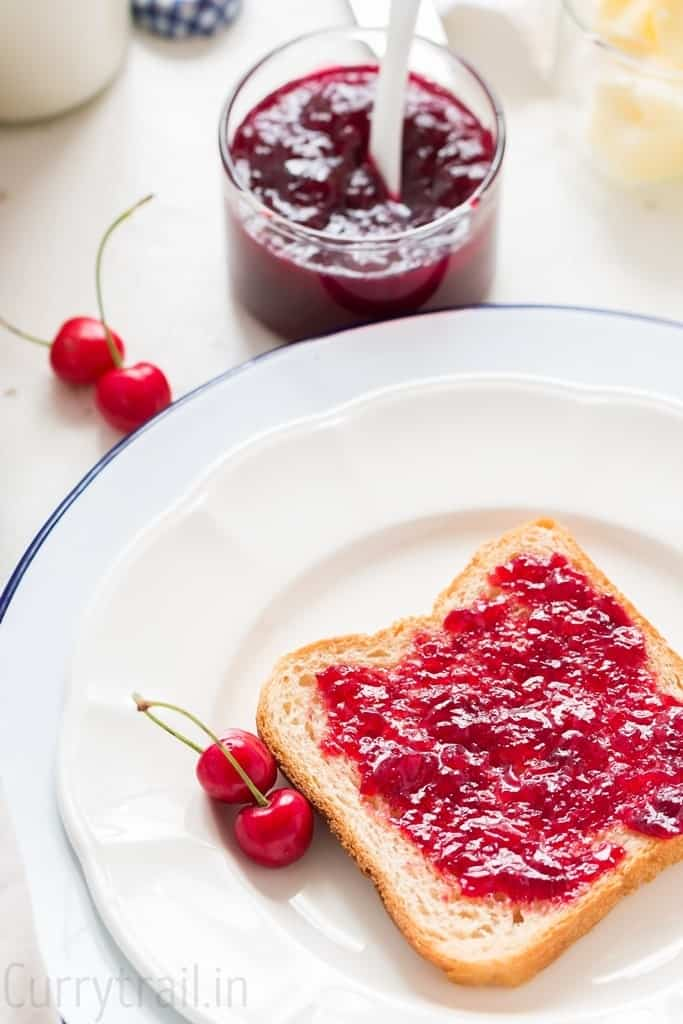 white plate with a bread slice smeared with homemade cherry jam