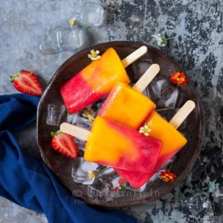 4 strawberry mango popsicles placed on round metal tray with ice cubes and pretty flowers on it
