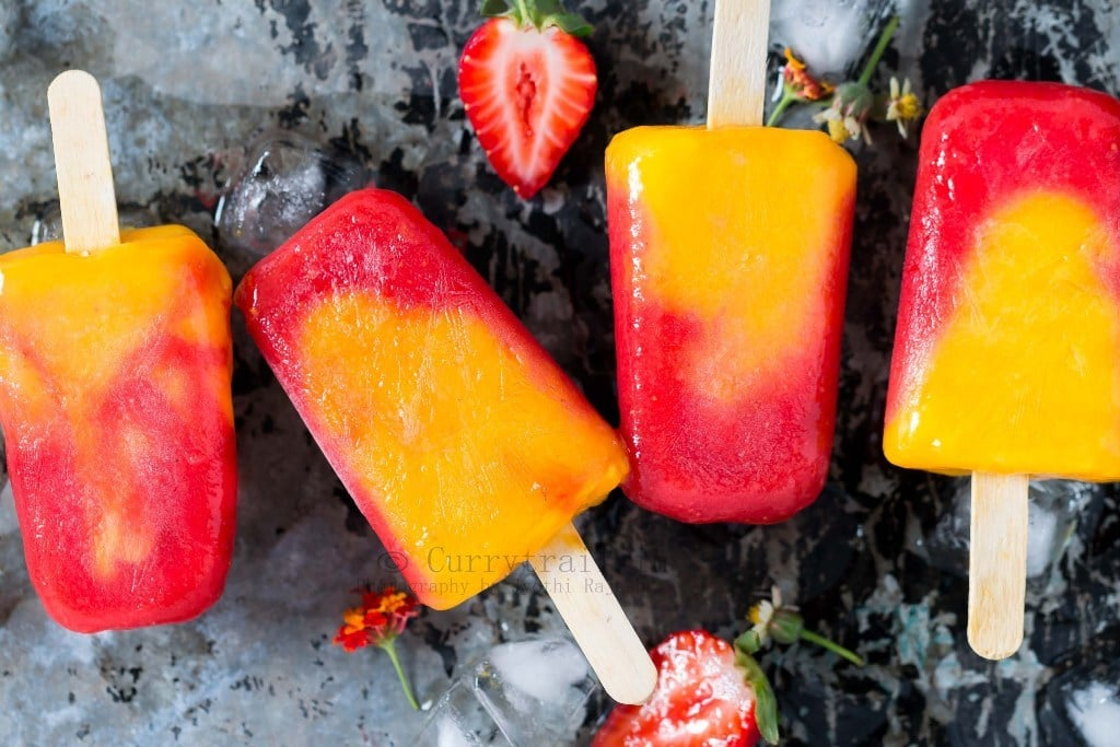 4 strawberry mango popsicles lined on a rustic metal plate with ice cubes