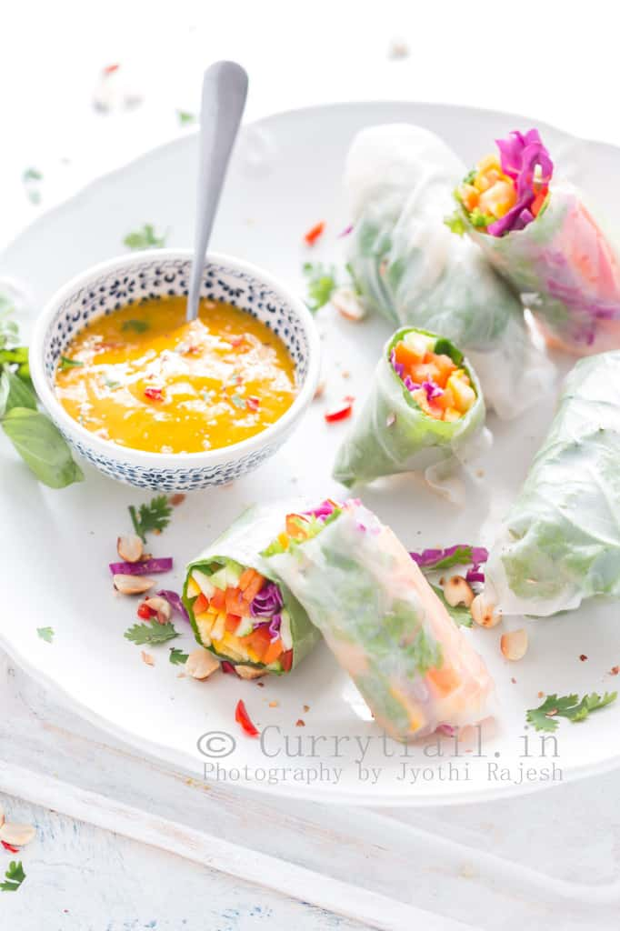 Thai rice paper rolls with mango dipping sauce in white plate