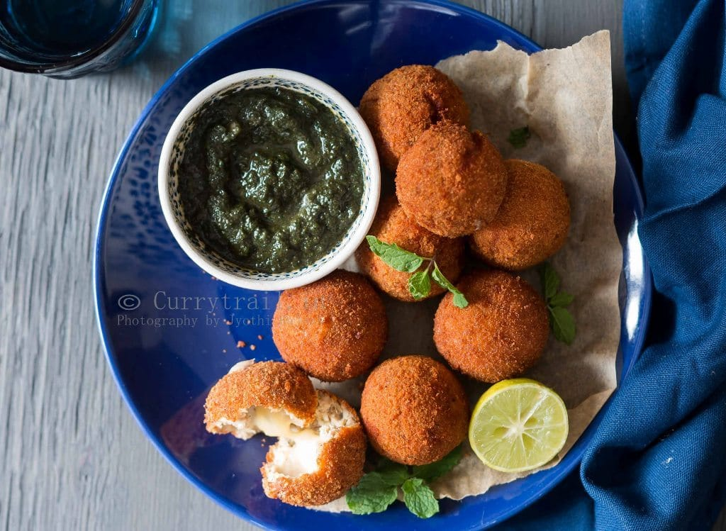 a blue plate with cheesy garlic chicken balls with a small bowl of mint sauce on side