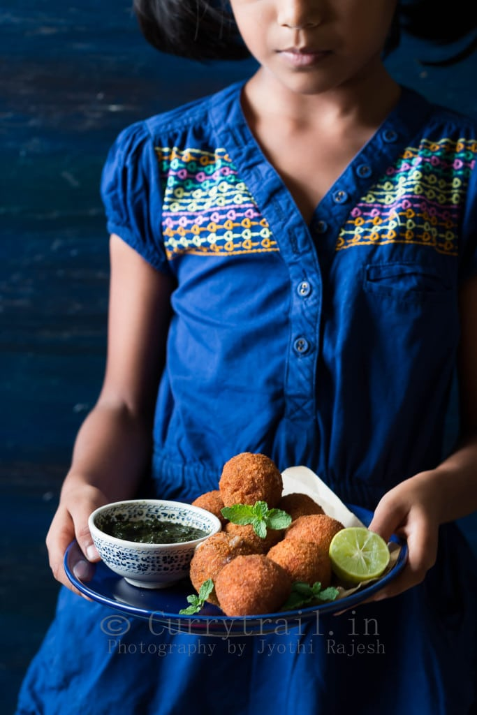 Little girl holding a blue plate full of cheese stuffed garlic chicken balls along with mint sauce