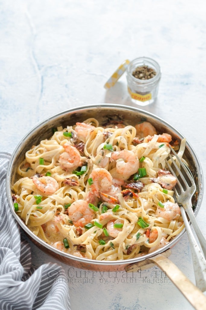 Garlic Shrimp Pasta in Creamy Sauce In a Pan and seasoning bottle