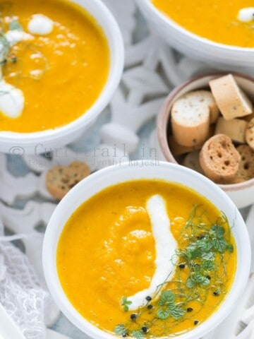 3 white bowls of roasted carrot soup served on white tray with roasted bread on side