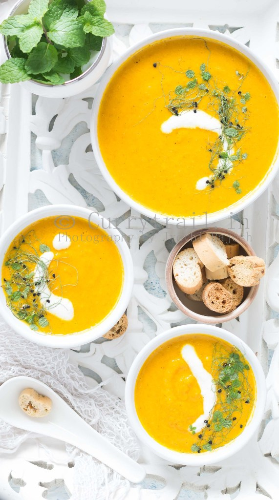 roasted carrot soup served in white bowl with roasted bread on side