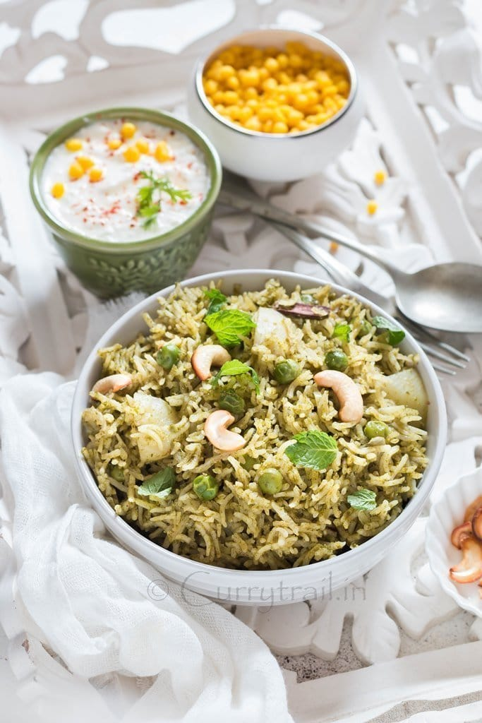 Homemade Mint Pulao in white bowl with raita on the side