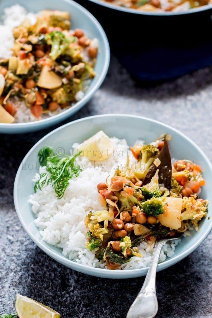 Blue bowl of rice with vegetable chickpea curry on top