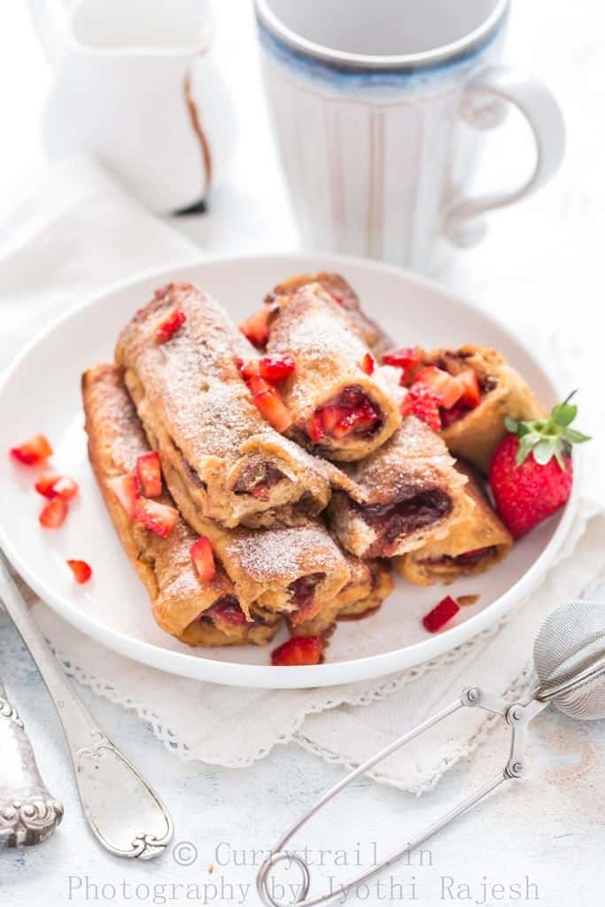Nutella Strawberry French toast Roll Ups stacked up on white plate with morning coffee on the back