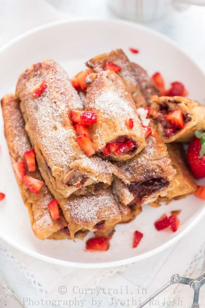 French toast roll ups with Nutella and strawberries stacked on a white plate