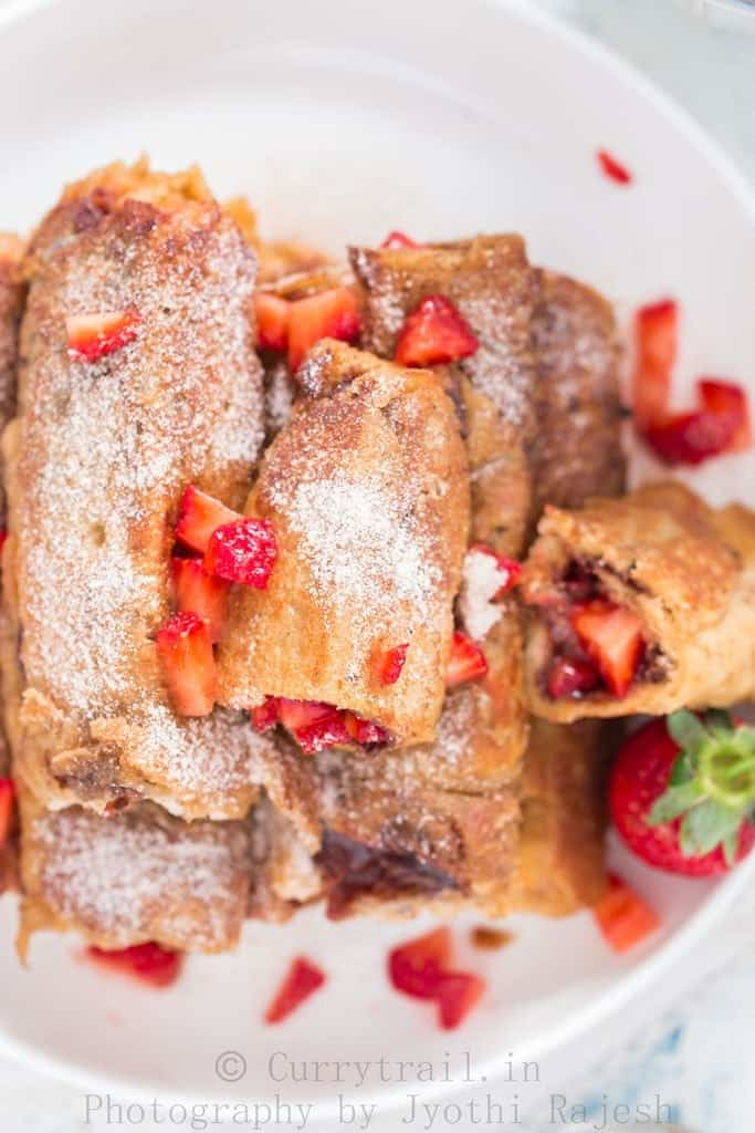 on a white plate Nutella Strawberry French toast Roll Ups stacked up