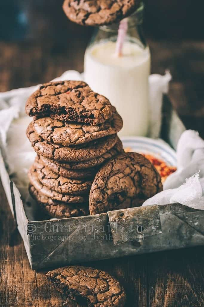 dark chocolate chili cookies served in rustic tray with bottle of milk on the side