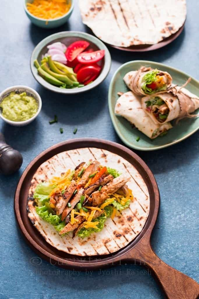 Flour tortillas with chicken fajitas with a plate and bowls around