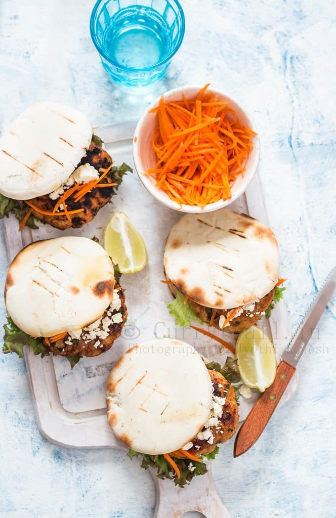 Moroccan Chicken Burgers Spread on a Boards with Bowl of carrots in top view