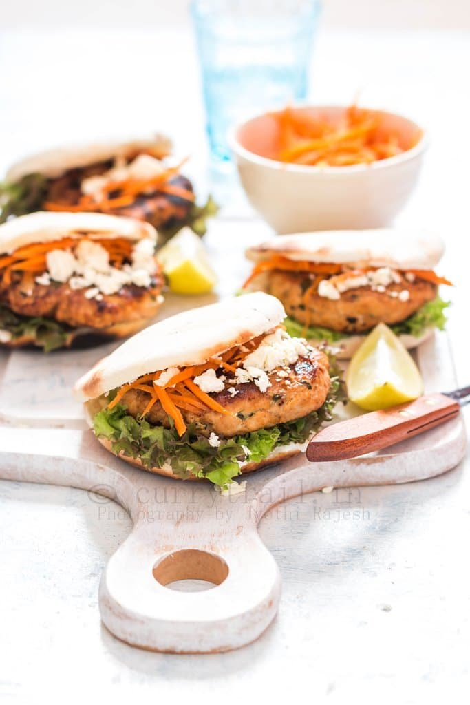 Moroccan Chicken Burgers Spread on a Boards with Bowl of carrots served on a board