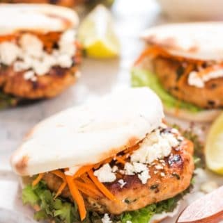 Moroccan Chicken Burgers Spread on a Boards with Bowl of Carrots close up view