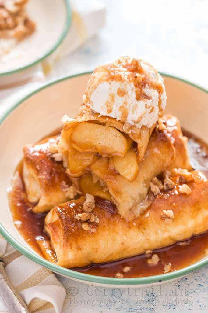 apple pie enchilafa with nuts on top drizzled with brown butter sauce and served with ice cream
