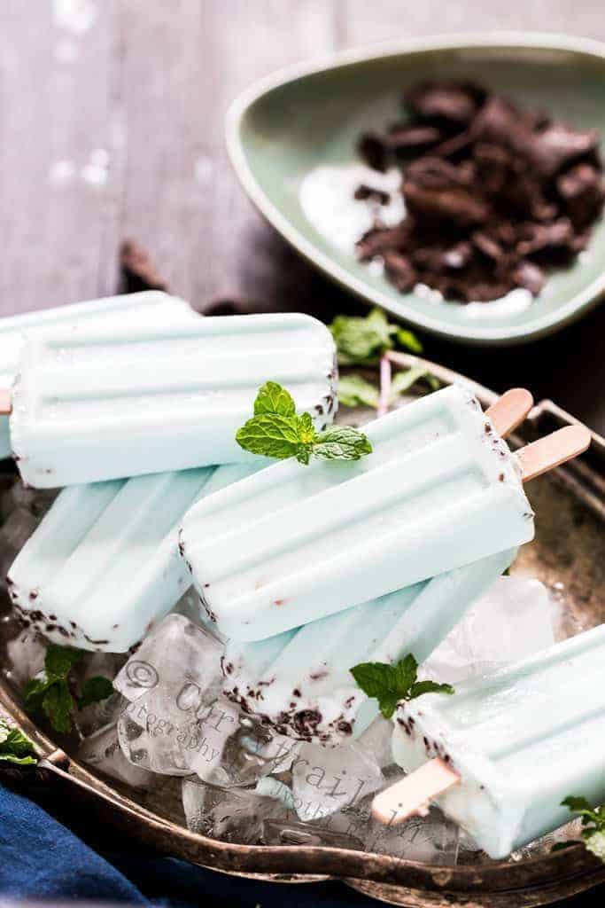 Healthy vegan mint chocolate popsicles on a tray of ice cubes