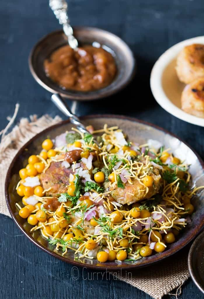 aloo tikki chaat served in ceramic plate with chutney on sides