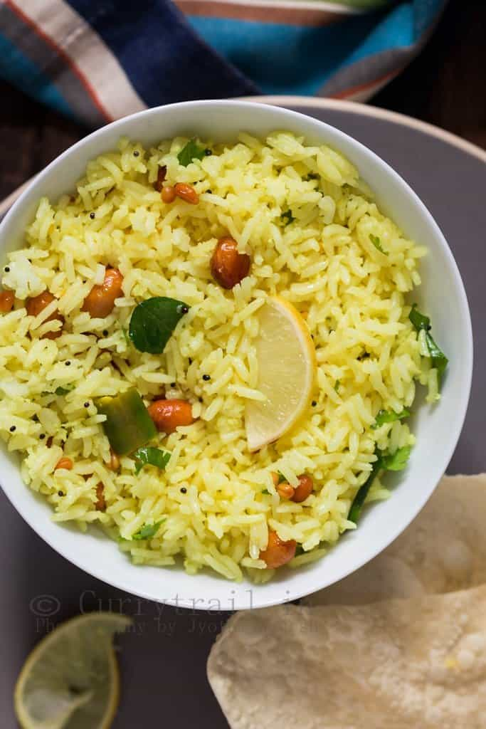 lemon rice served in small ceramic bowl with papad on the side