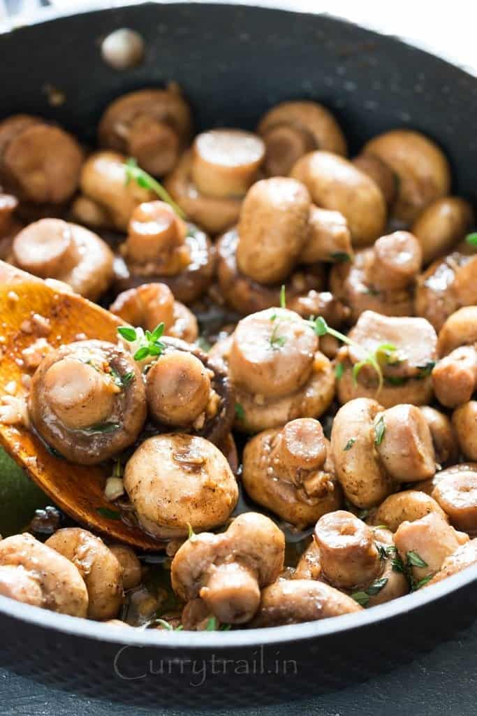 cooking sauteed mushroom recipe with butter garlic and thyme in skillet