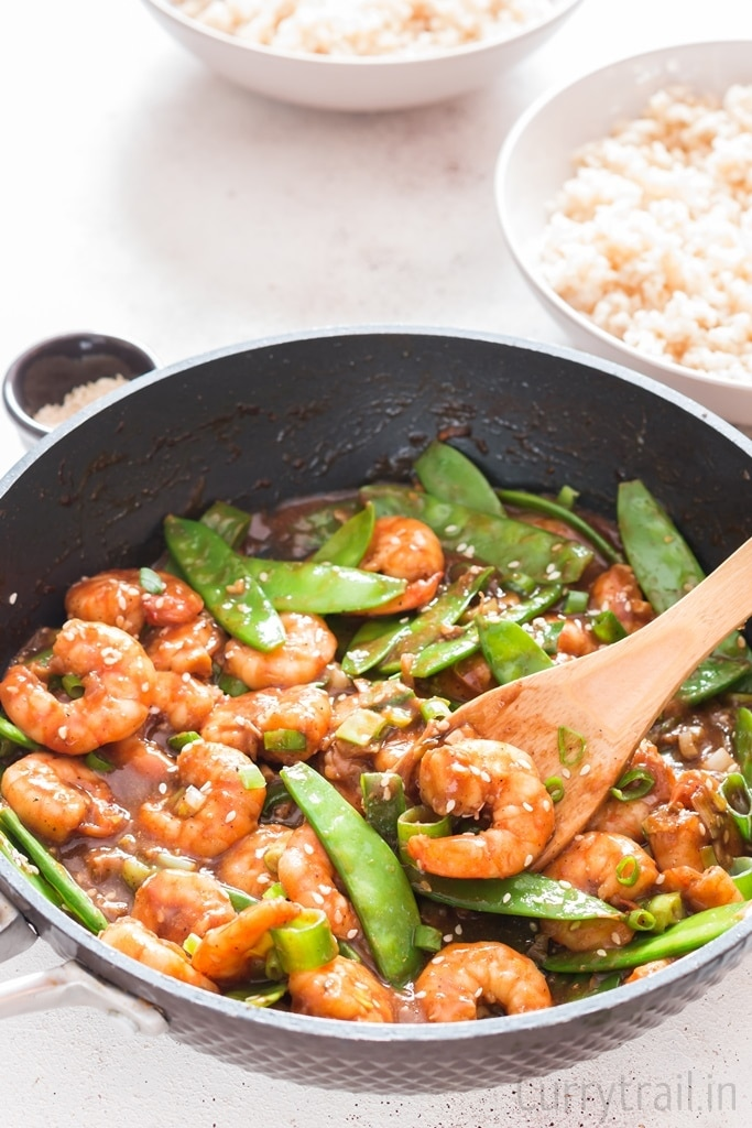 shrimp stir fry with snow peas garnished with spring onions and sesame seeds in a skillet pan