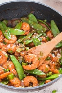 shrimp stir fry in a skillet with snow peas