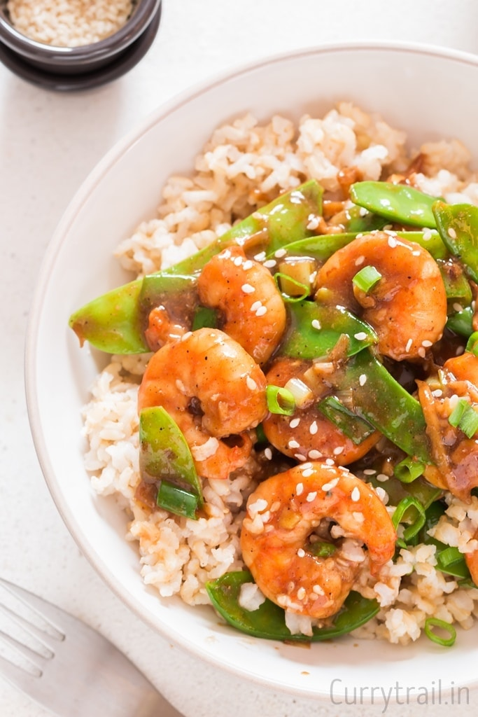 Rice and shrimp stir fry with snow peas in white bowl garnished with spring onions and sesame seeds