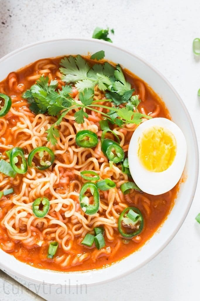 Soft boiled egg placed over a bowl of spicy sriracha ramen noodle soup in white bowl