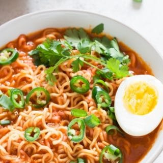 spicy sriracha ramen noodles soup with soft boiled egg in a white bowl