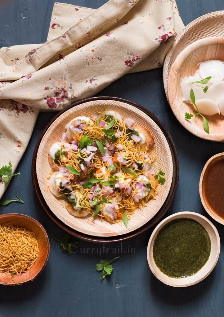 Idli chaat on a plate with chutney's on the side
