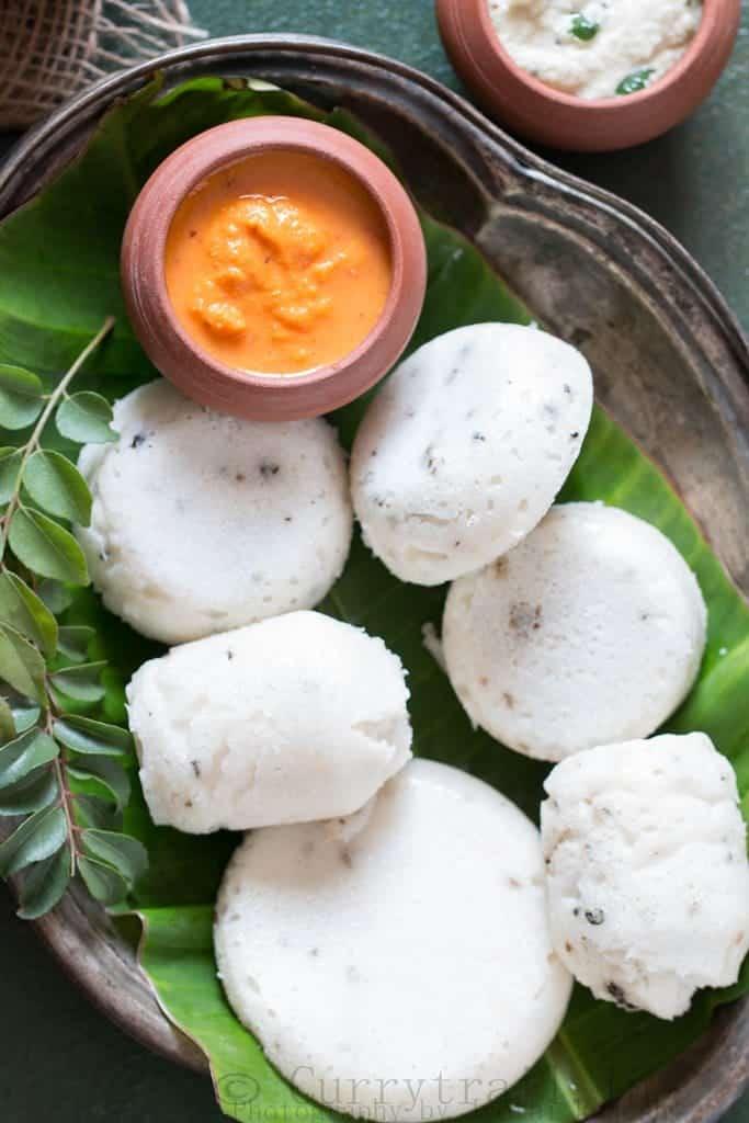 Kanchipuram Idli arranged on a oval plate with onion-tomato chutney on the side