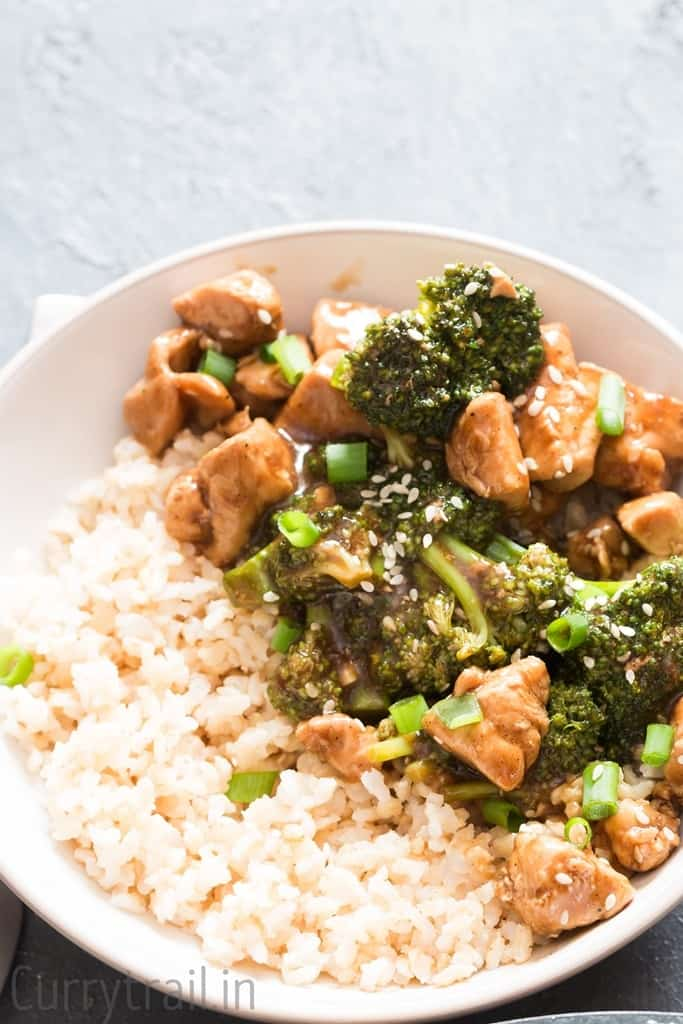 chicken rice and broccoli stir fry in a white bowl with brown rice