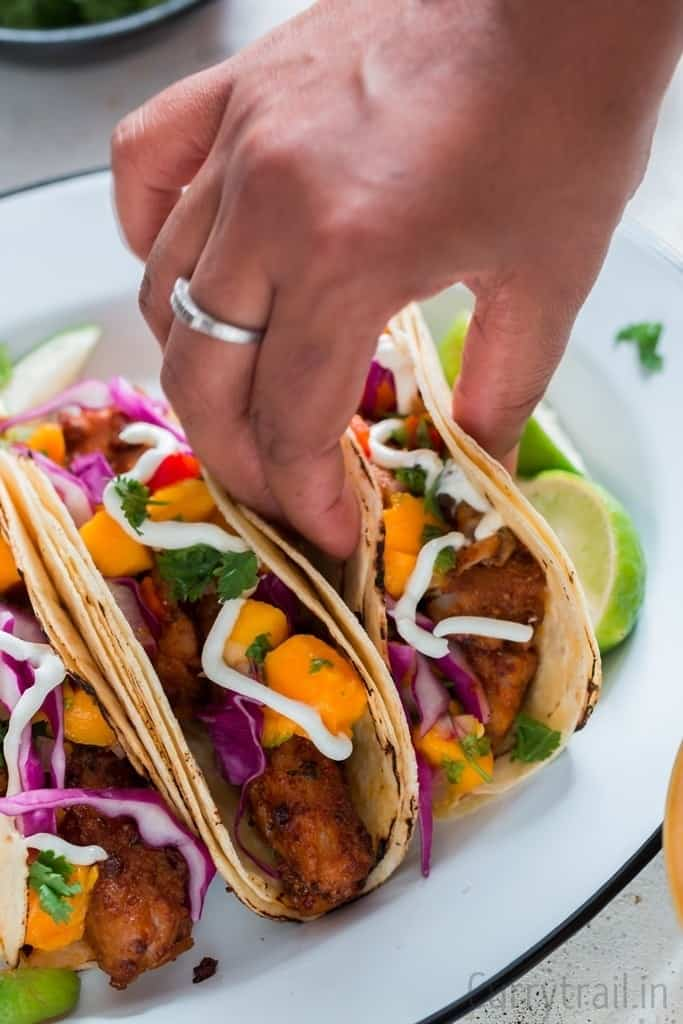 picking a tilapia fish taco placed on a enamel white plate