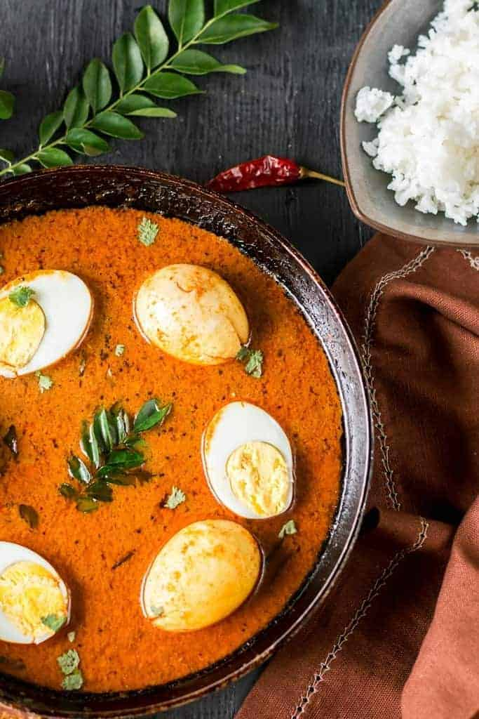 Chettinad egg curry served in pan with curry leaves on side and a bowl of rice