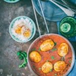 Dhaba style punjabi egg curry in a cooking pan with rice bowls on sides