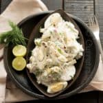 Creamy egg and potato salad mixed with dill leaves is the best summer salad served in black plates with lime on the sound