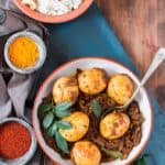 Spicy Kerala egg roast with spice bowls and curry leaves on the sides and coconut rice behind