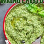 basil pesto with walnuts in small bowl with text